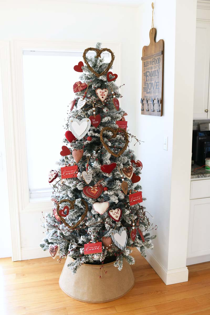 Farmhouse Valentine Tree with a burlap tree collar. There are red and white heart ornaments on this tree.
