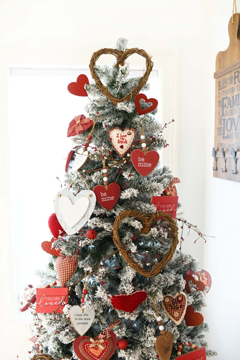 Farmhouse Valentine's Day Tree with wood, red, and white décor in a white room.