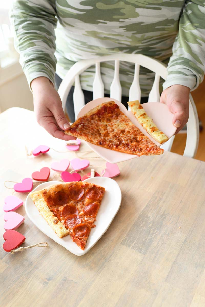 Hand holding Pizza Plates. A woman with camo on is placing pizza on heart shaped plates onto the table.