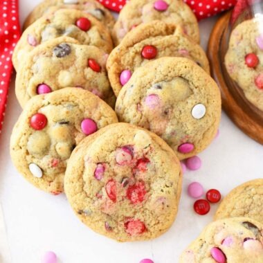 JUMBO Chewy M&M Chocolate Chip Cookies are spread on near a red dot napkin on a white table. There are 11 cookies in this image with Valentine's M&Ms scattered around.