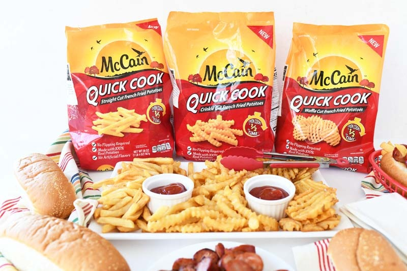 McCain Quick Cook fries in the package and prepared on a rectangle plate. There is Chourico and bread nearby.