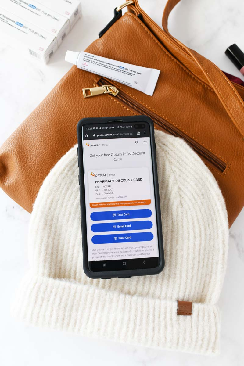 Optum Perks savings mobile app on a cream hat. There is a tan purse and prescription cream tube nearby.