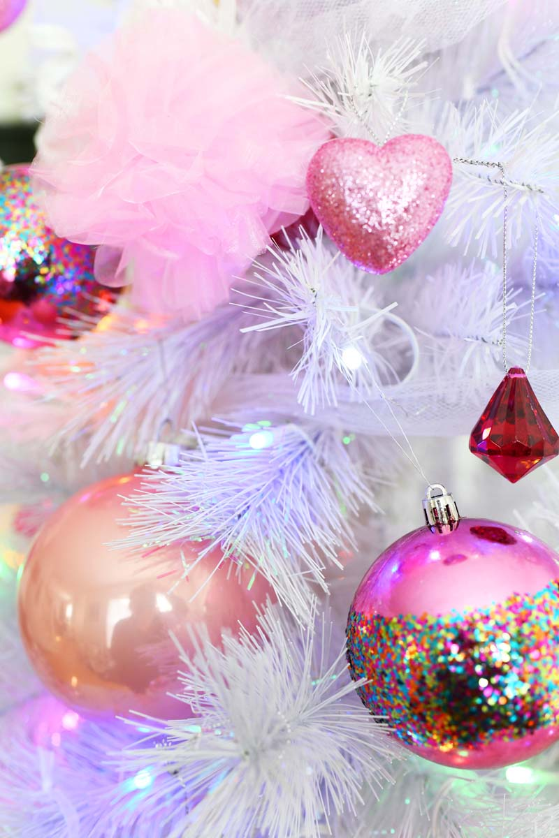 Pink ornaments on a white tree with jumbo pink balls and colorful lights.