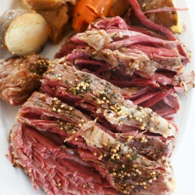 Sliced, cooked slow cooked corned beef with cooked cabbage, carrot, and potato on a white oval platter.