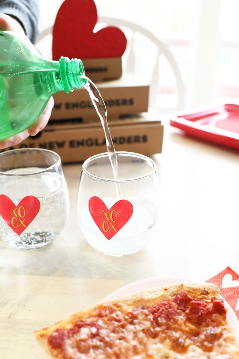 Sierra Mist is pouring into two pink heart glasses on a table near pizza.