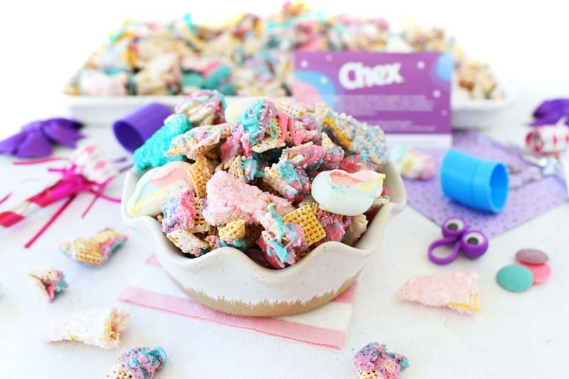 Unicorn Chex Mix in a bowl with snack pieces nearby. There are little trinkets around.