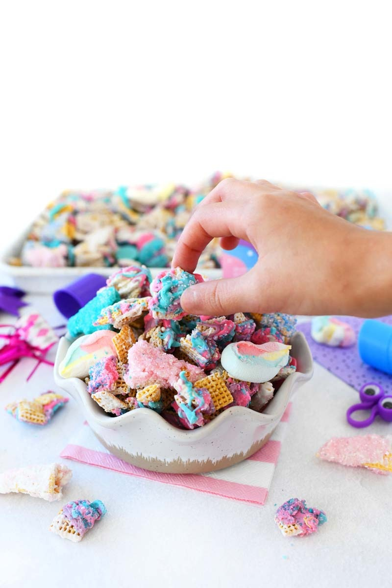 Unicorn Snack Mix Recipe with a hand picking the pieces out.