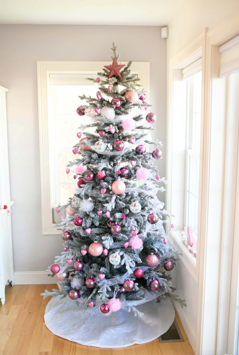 Valentine's Day Tree in a grey room. There is pink and white ornaments on this green tree.