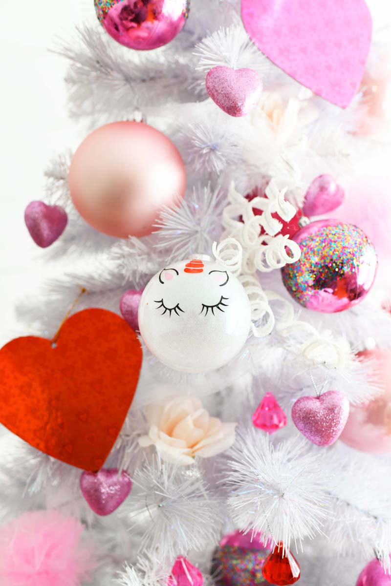 Whimsical Valentines Day Tree up close with pink and red ornaments.