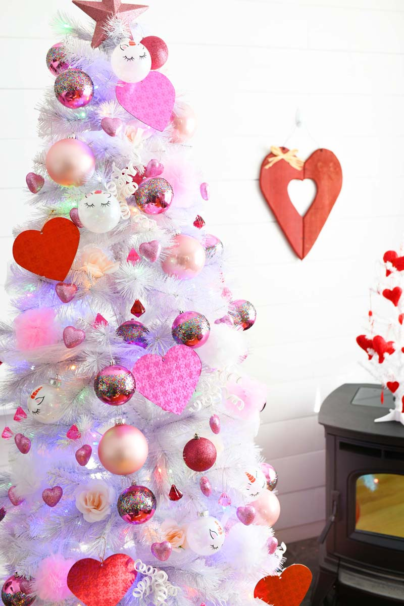 White Valentines Day Tree in a white living room. There is a red heart on the wall.