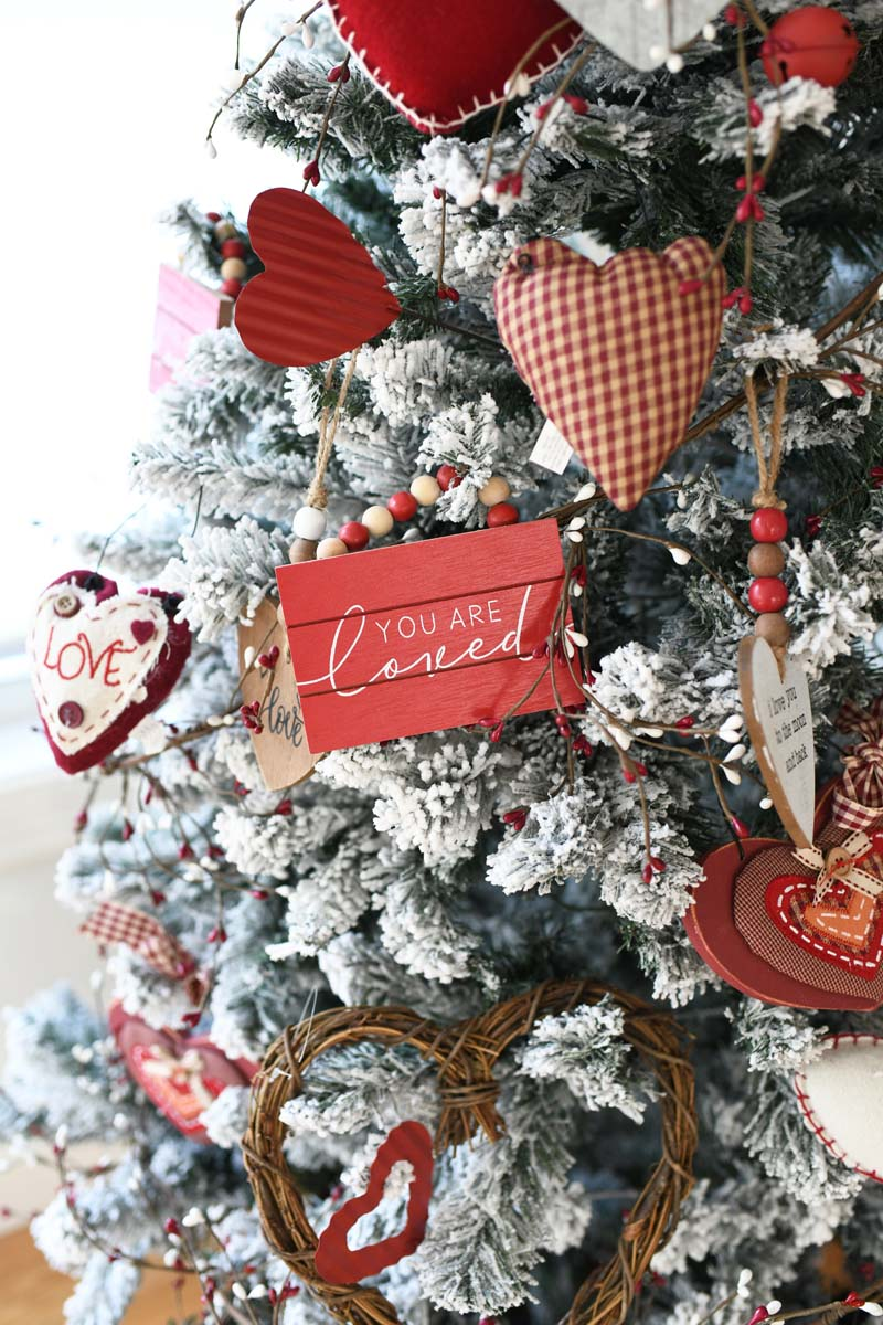 You are loved ornament on a flocked tree. There are red and white Valentines Day Ornaments on this tree.