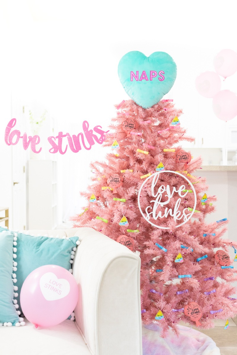 Pink, Fluffy Love Stinks Tree. This tree has a teal heart topper, and pastel decorations. It is set in a light and bright room.