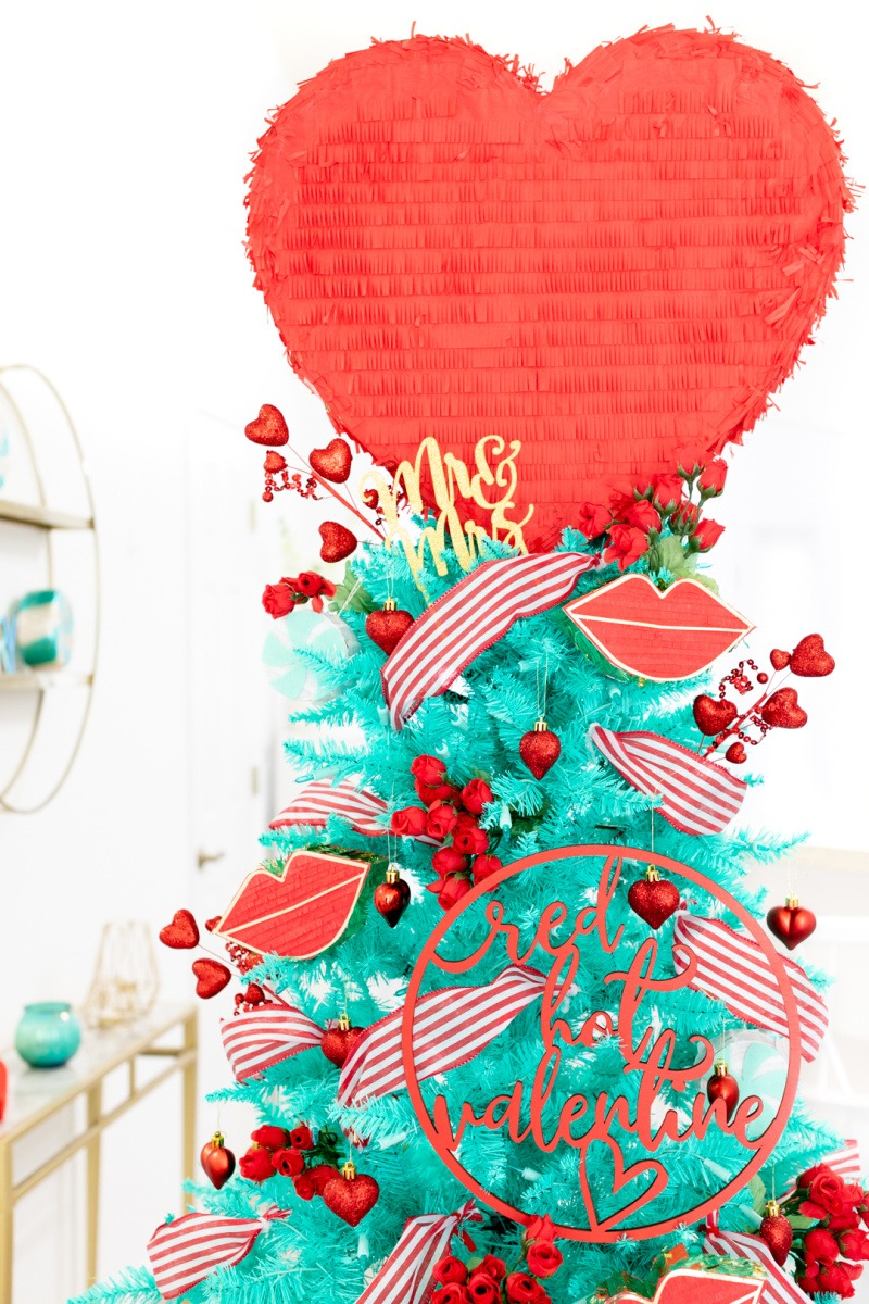 Romantic Valentines Day Tree Idea. A red and teal Valentine's Day tree with a jumbo heart pinata topper. There is red and pink décor on this tree.