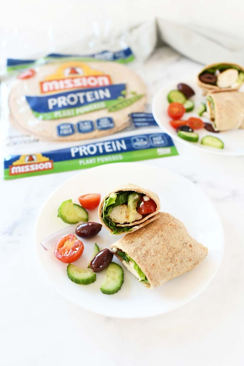 Greek Protein Wrap on a white marble table. The wrap in on a small, white bowl.