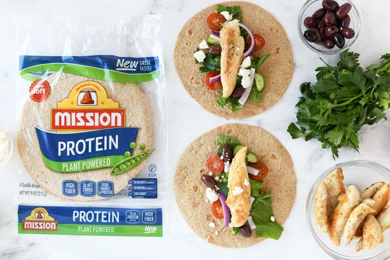 Greek Salad Protein Wraps on a white marble table. The wraps are assembled, but not rolled.