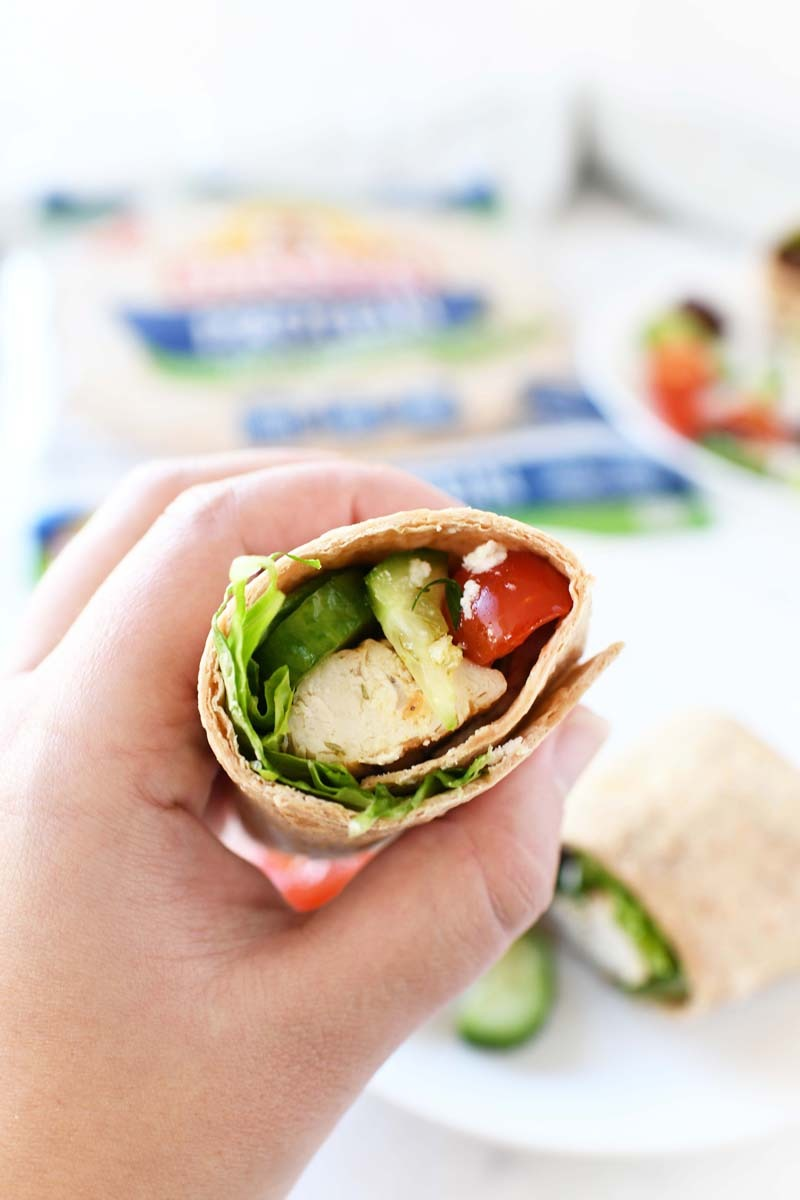Greek Wrap recipe in someone's hand showing inside the wrap.