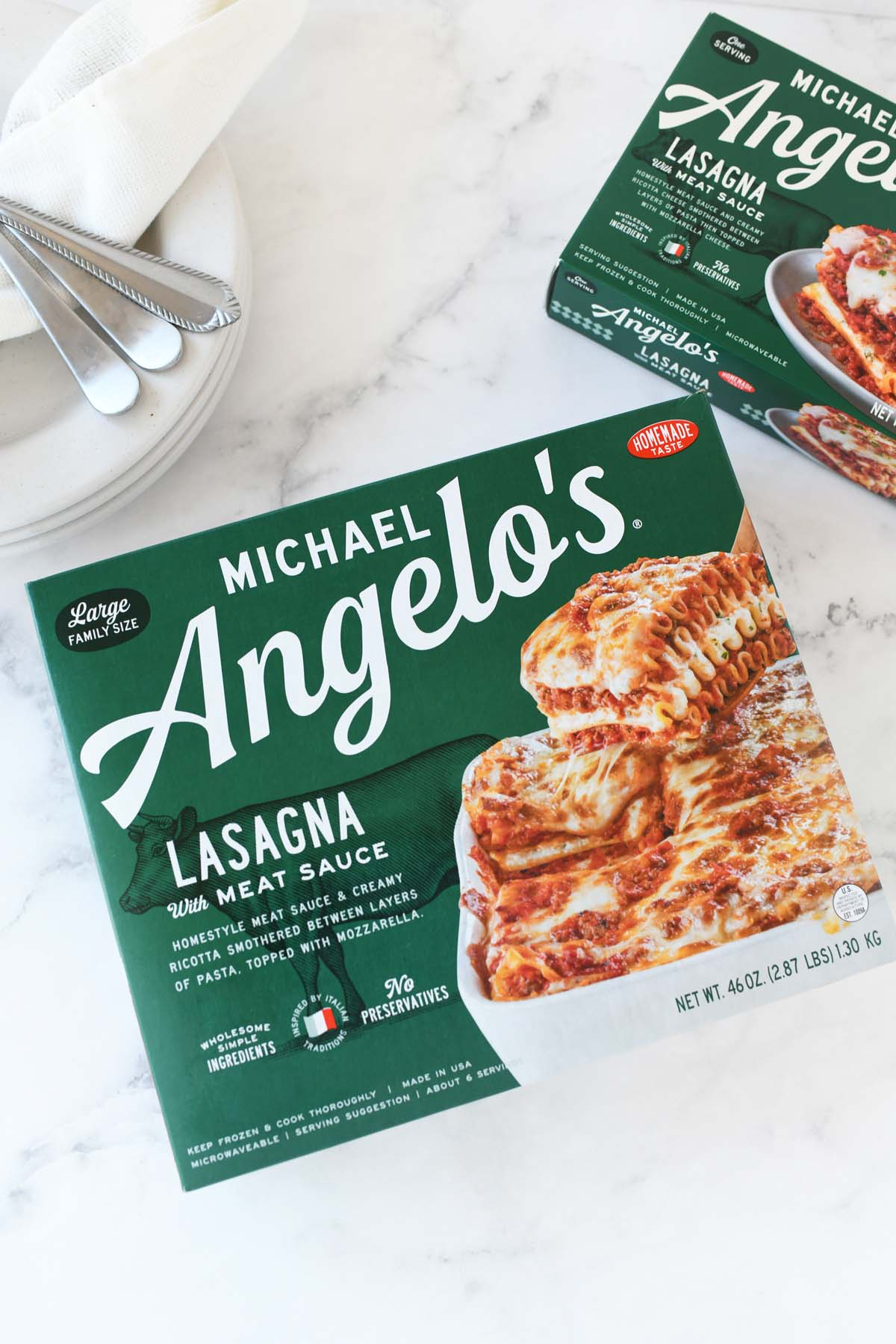 Michael Angelo's Large Family Size product box on a white marble table with plates and cutlery.