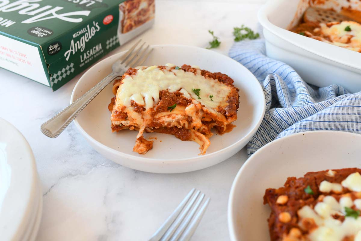 Michael Angelos Lasagna Slices on plates. There is a product box, and forks in the image as well.
