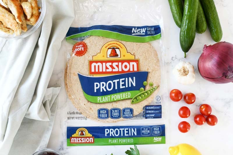Mission Protein Greek Chicken Salad Wraps on a white marble table with fresh vegetable ingredients.