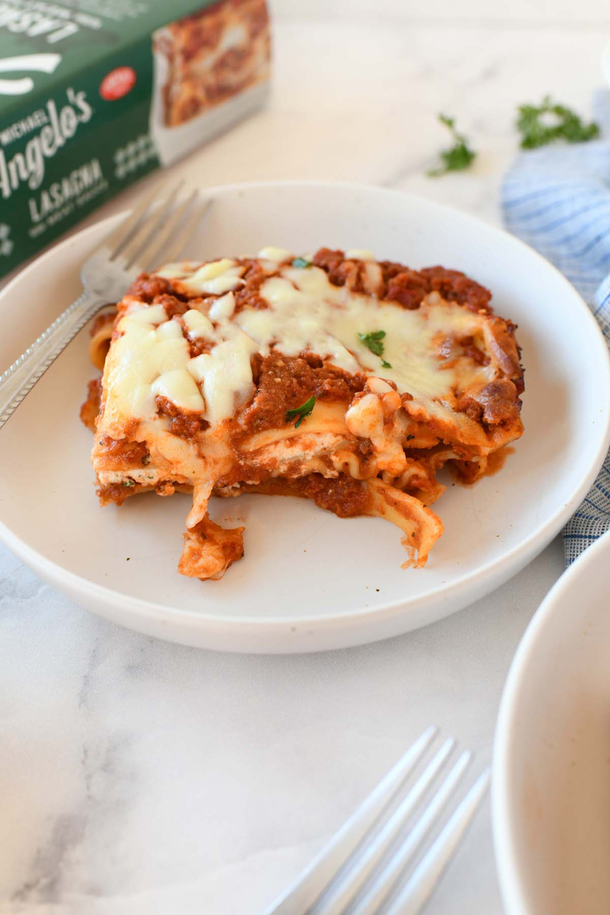 Slice of Lasagna on a small white plate with a fork.