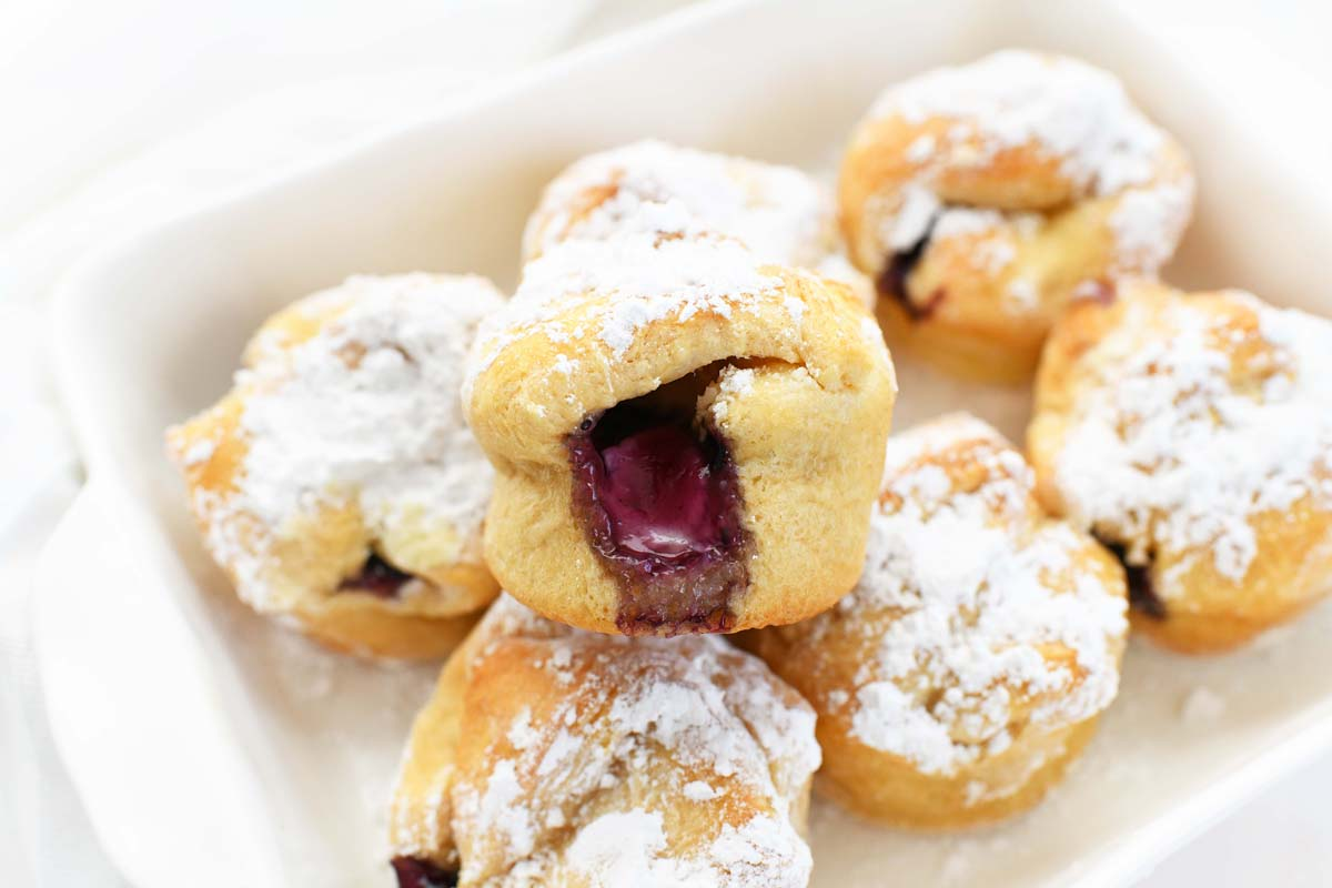 Blueberry Crescent Bites stacked in a ceramic plate with powdered sugar on top.