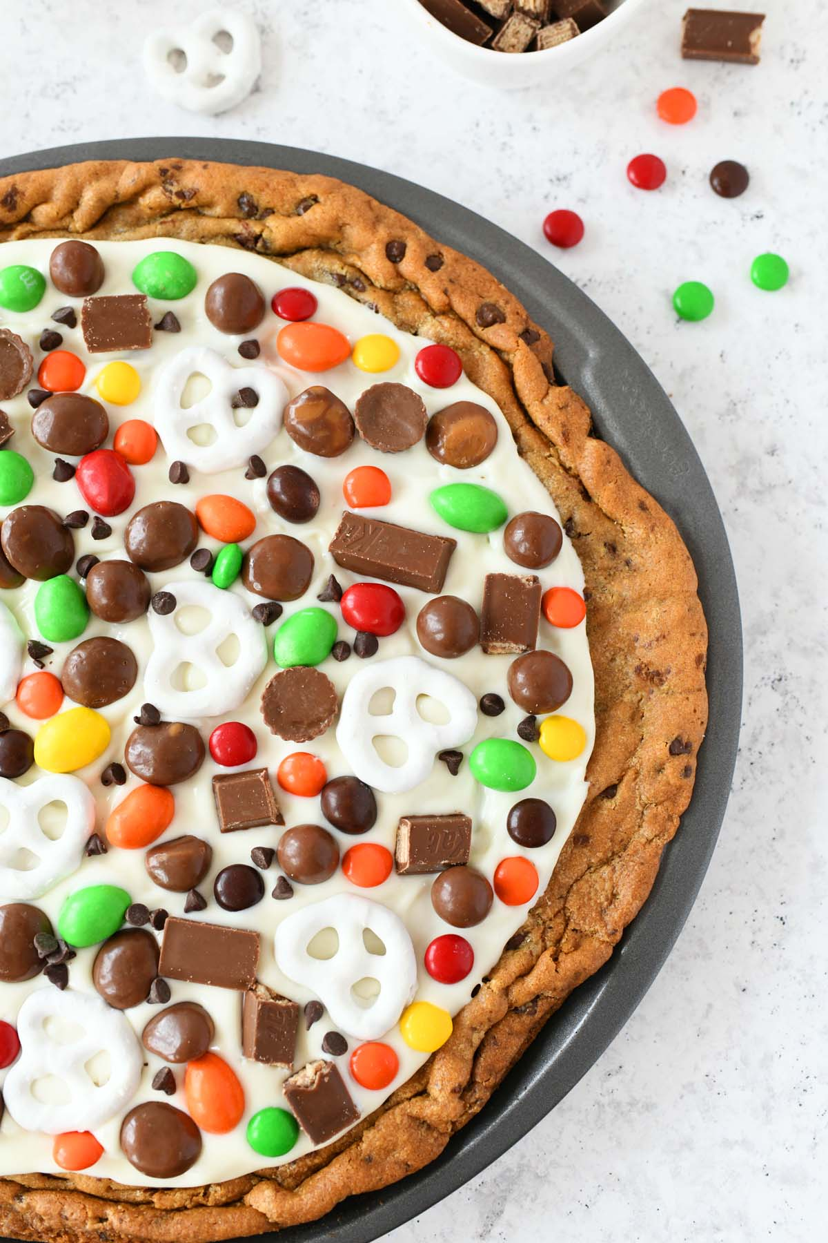 Chocolate Chip Cookie Pizza in a pan topped with white chocolate candy pieces.
