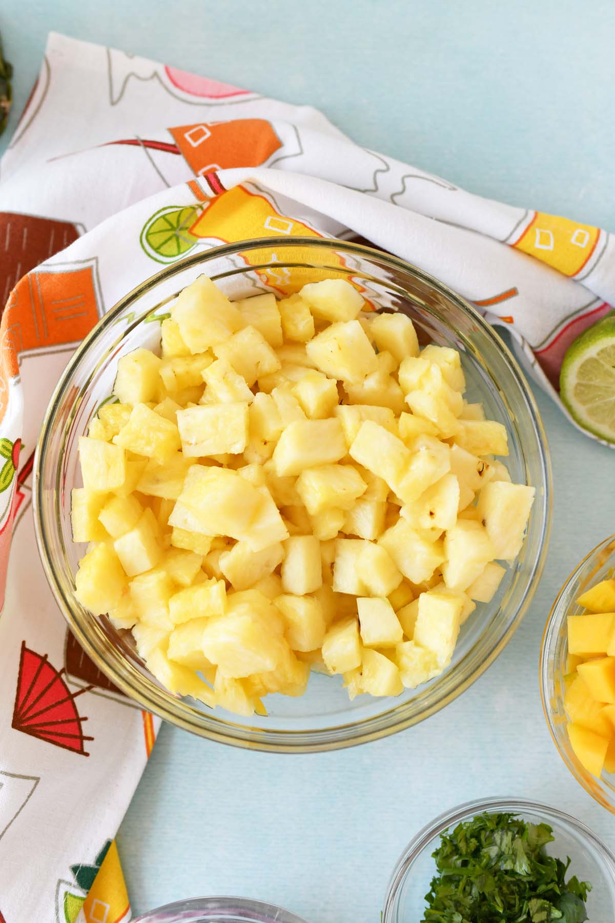 Cubed pineapple for salsa in a large glass bowl on a blue table.