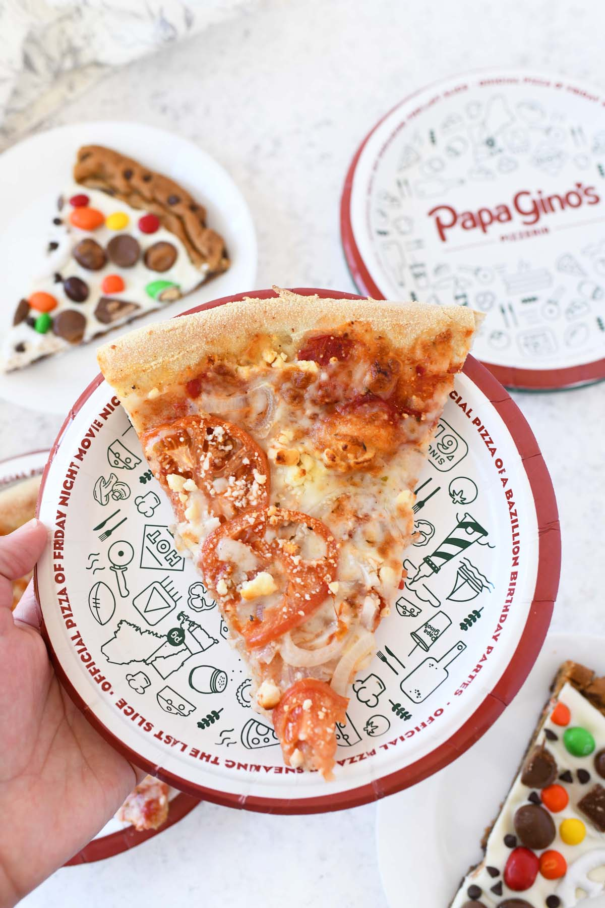Feta and Tomato Pizza on a Papa Gino's pizza plate in a hand.