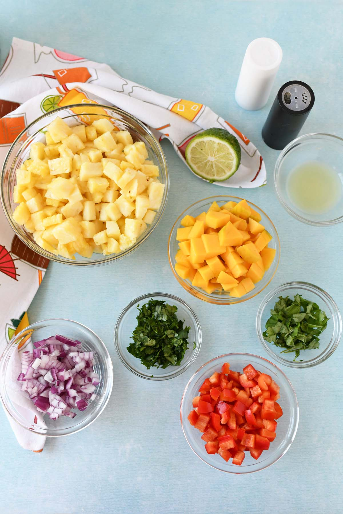 Fresh fruit and vegetables in mini glass bowls that make up pineapple mango salsa ingredients on a blue table.