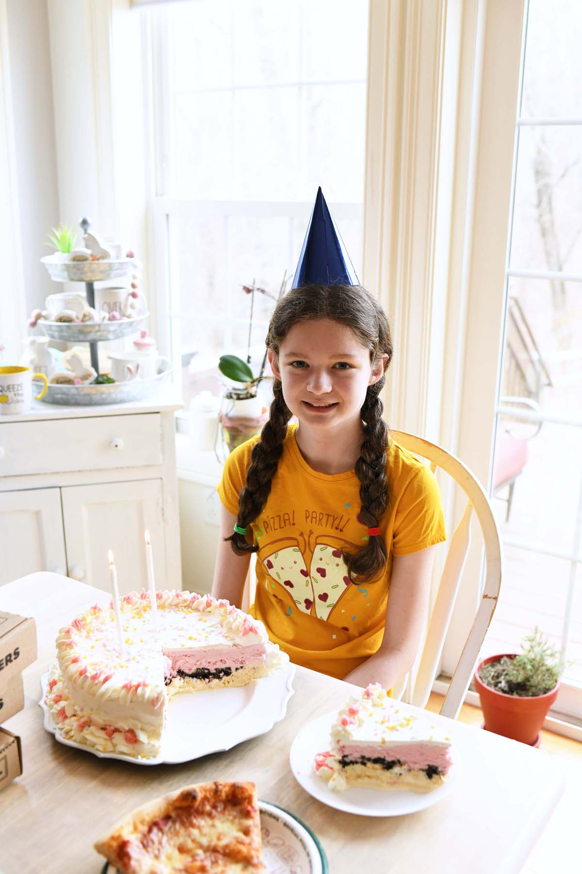 Girl at a Pizza Party with a blue party hat on.