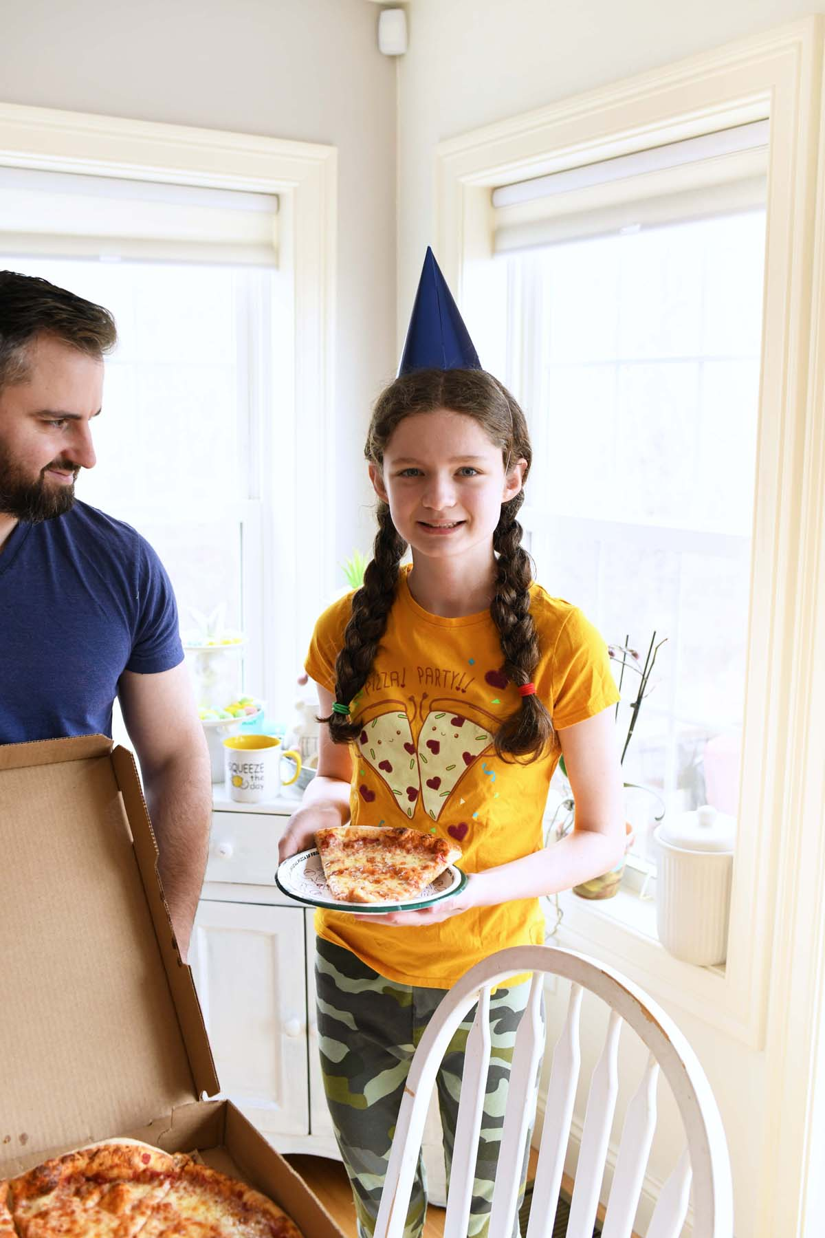 Girl with blue party hate on holding pizza with her father.