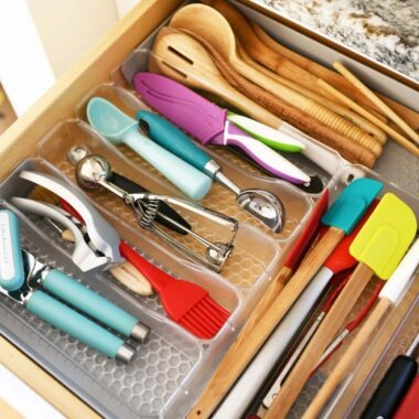 An organized kitchen tools drawer with colorful tools inside.