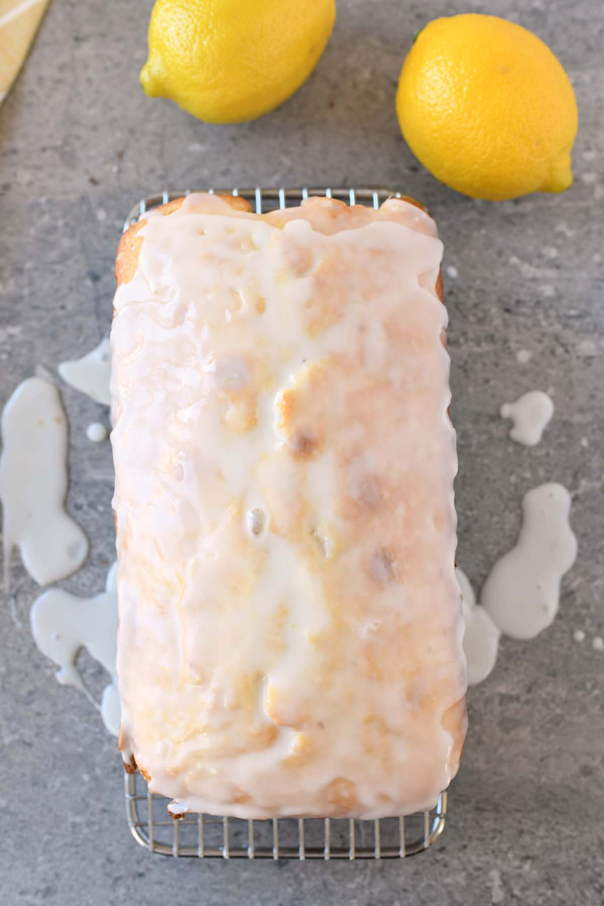 Iced Lemon Pound Cake on a cooling rack. There are 2 yellow lemon in the shot as well.