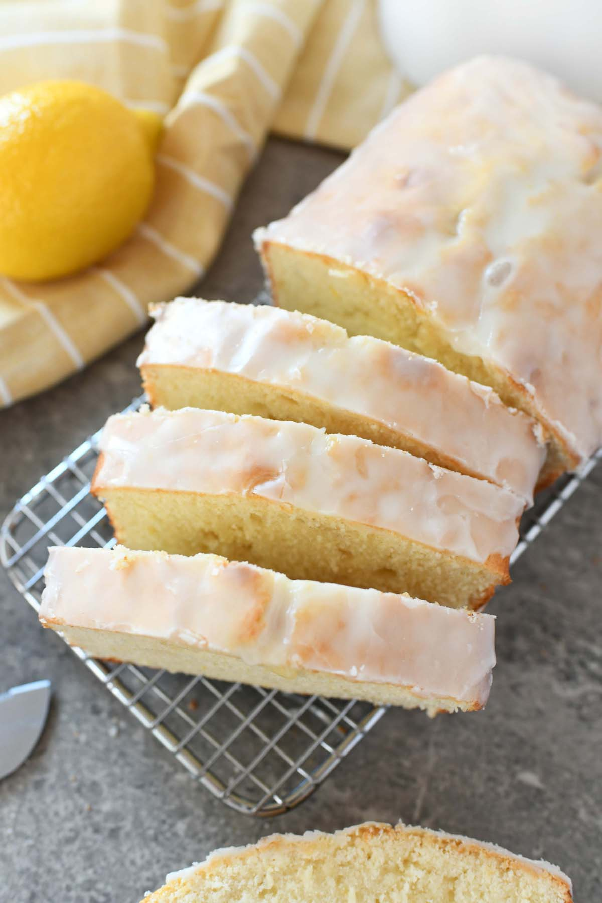 Iced Lemon Pound Cake Recipe. Sliced lemon pound cake is on a cooling rack with lemon and a yellow striped napkin nearby.