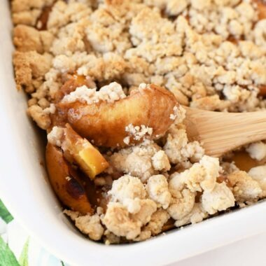 Juicy Peach Crumble baked in a white, rectangle baker with some crumble on a wooden spoon.