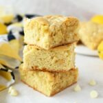 Lemon Blondies stacked on a white marble table with mini white chocolate chips.