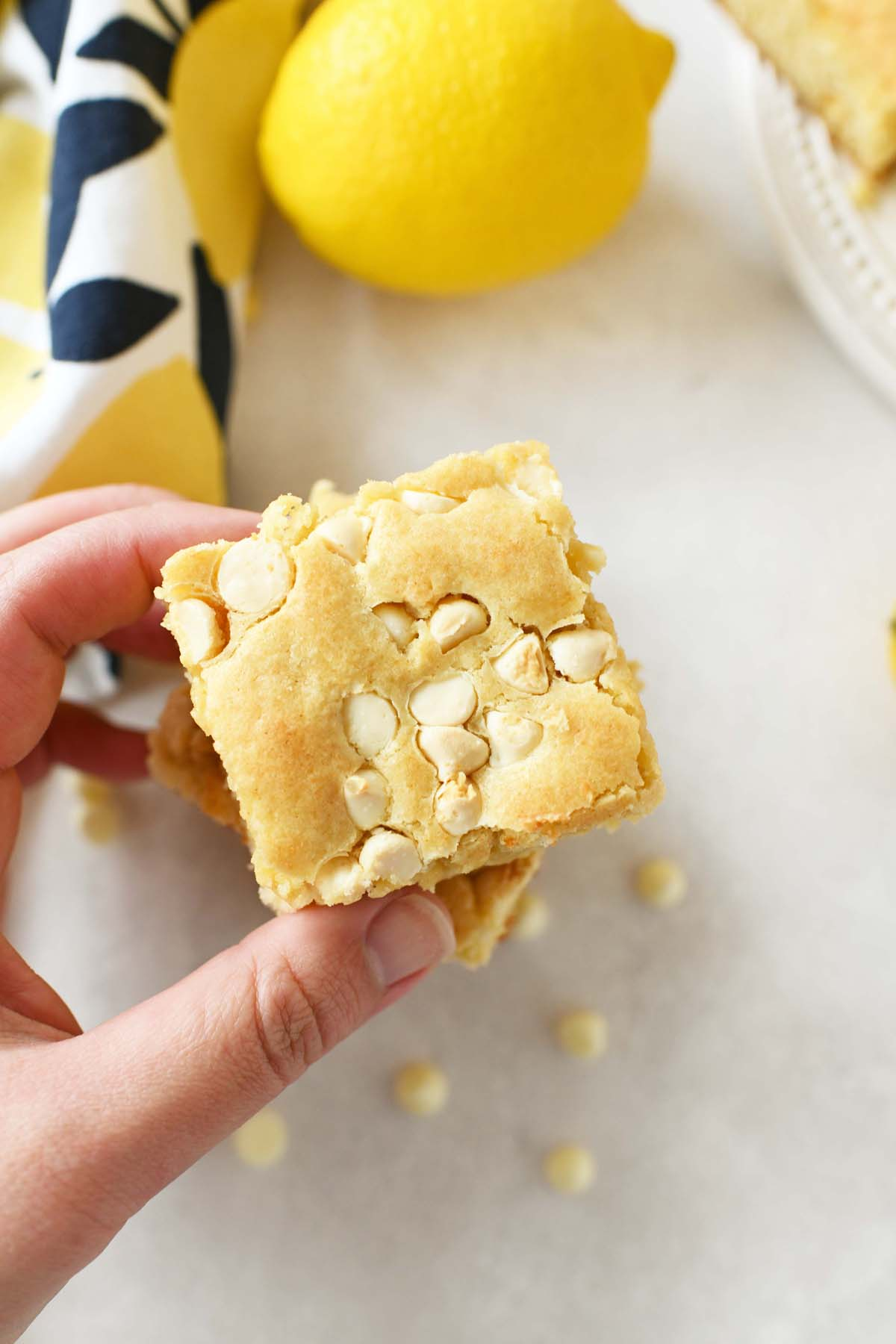 Lemon Brownies on a table with a white hand reaching for one.
