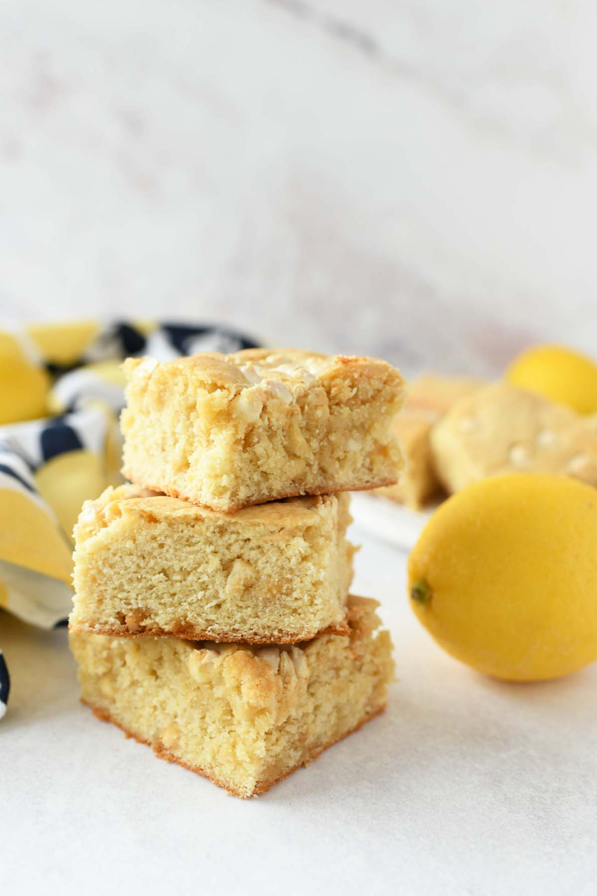 Lemon Cake Brownies are stacked on a marble table with fresh lemons nearby.