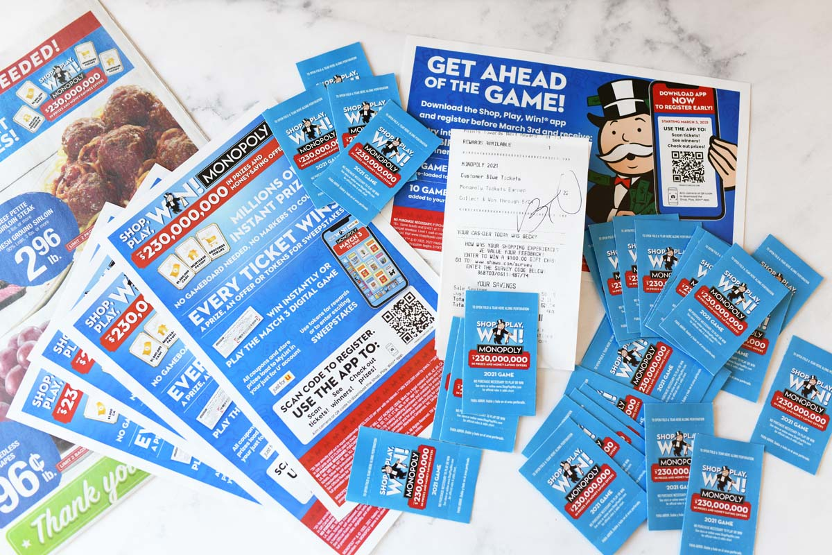 Shop, Play, Win game pieces and flyers spread out on a white table.