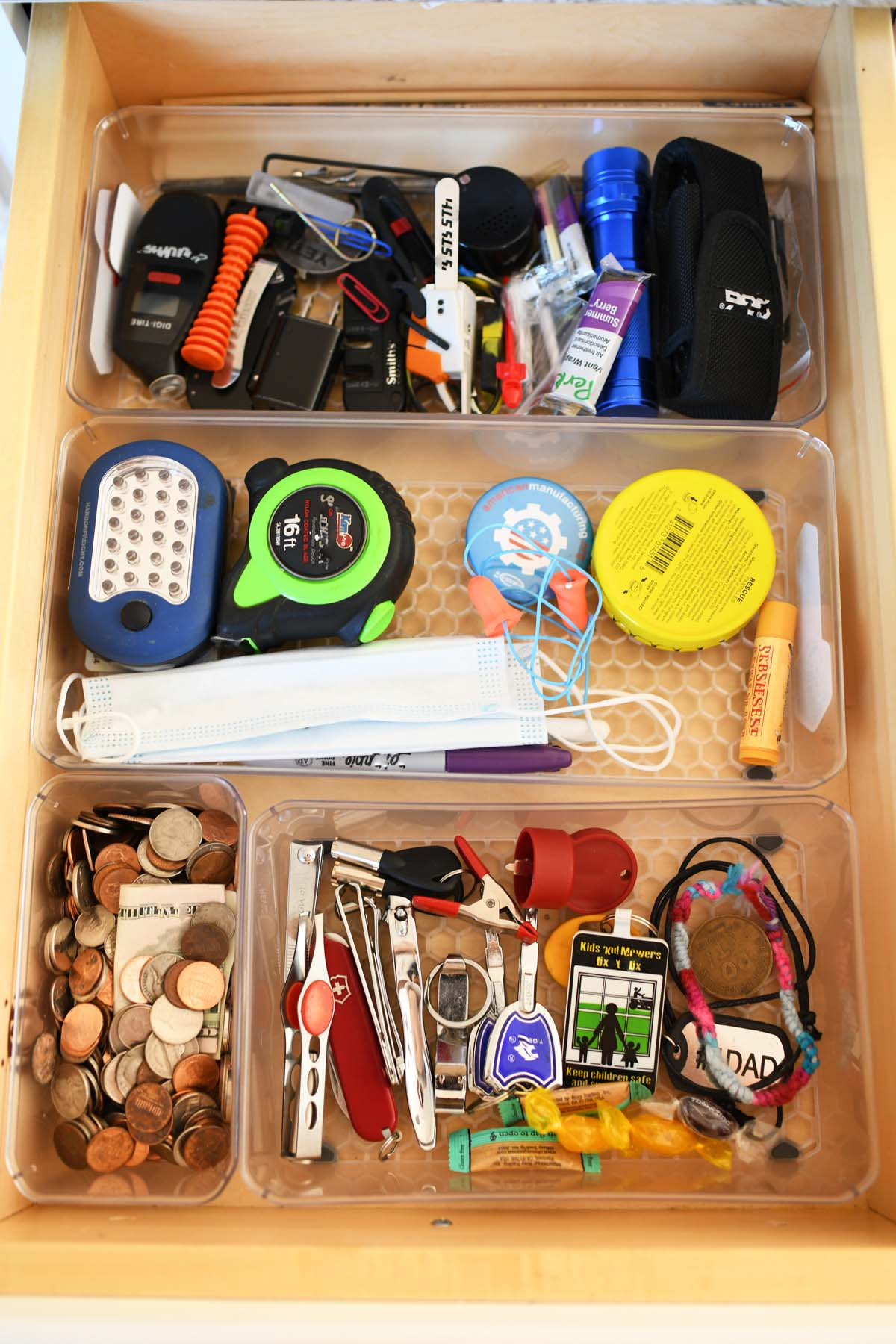 Organized Junk Drawer - A man's organized junk drawer with various tools.