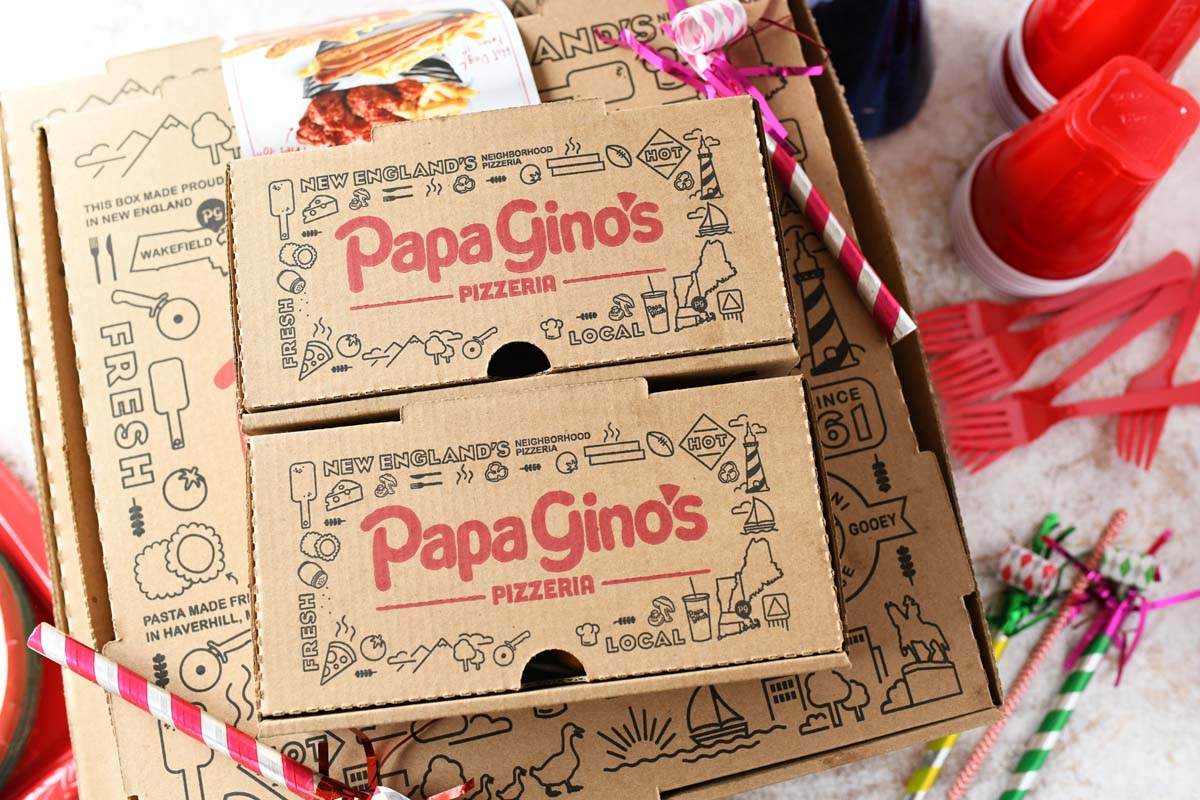 Papa Gino's Pizza boxes with birthday party supplies and red cups on a table.