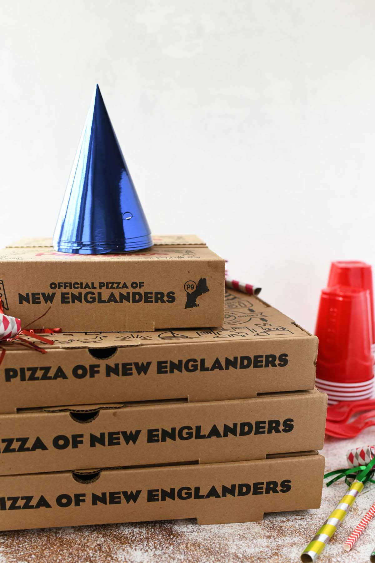 Papa Gino's boxes on a table with blue birthday hats on top.