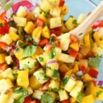Pineapple Mango Salsa in a glass bowl with a wooden spoon.