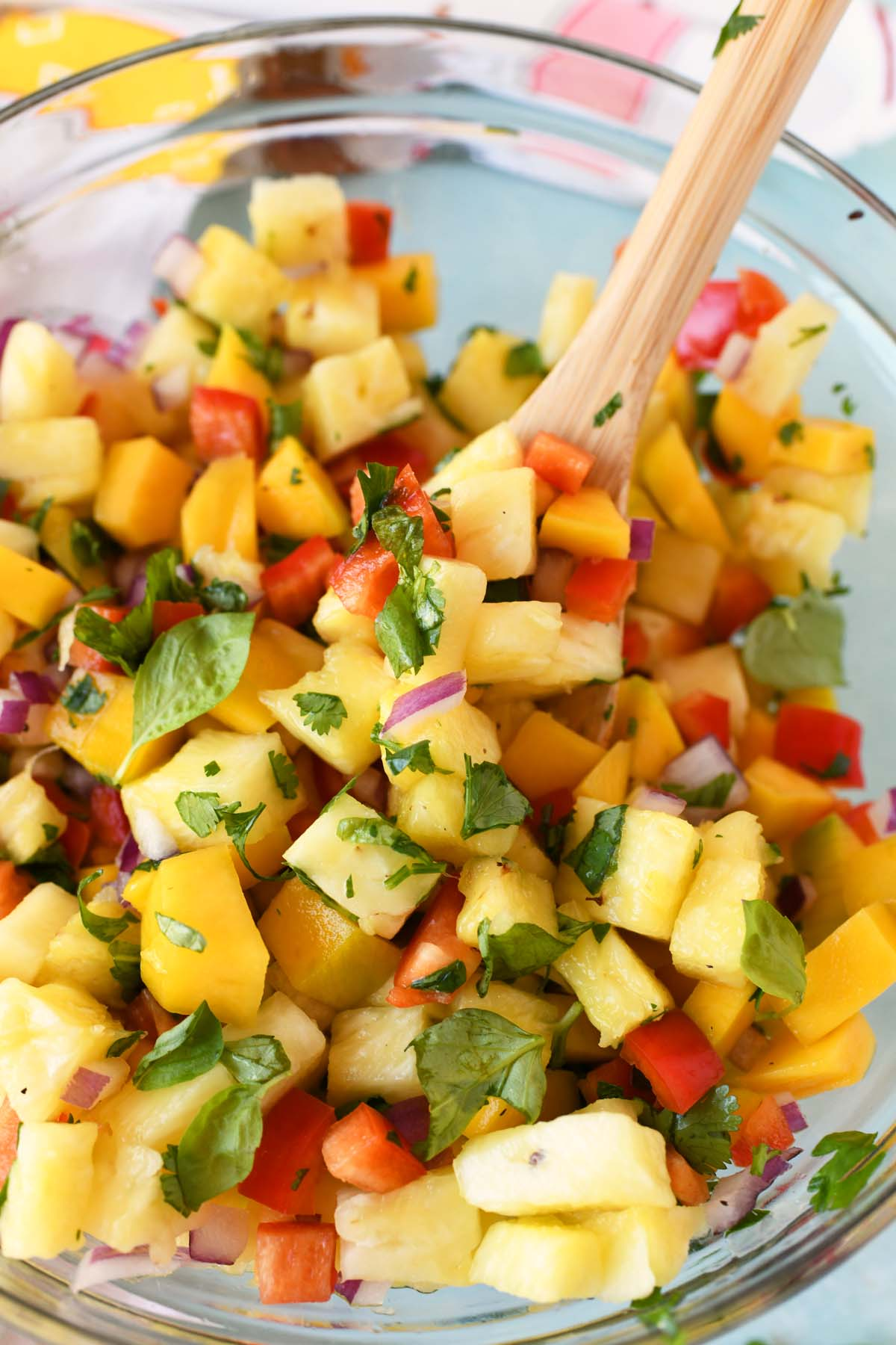 Pineapple Mango Salsa Recipe in a glass bowl with a wooden spoon inside.