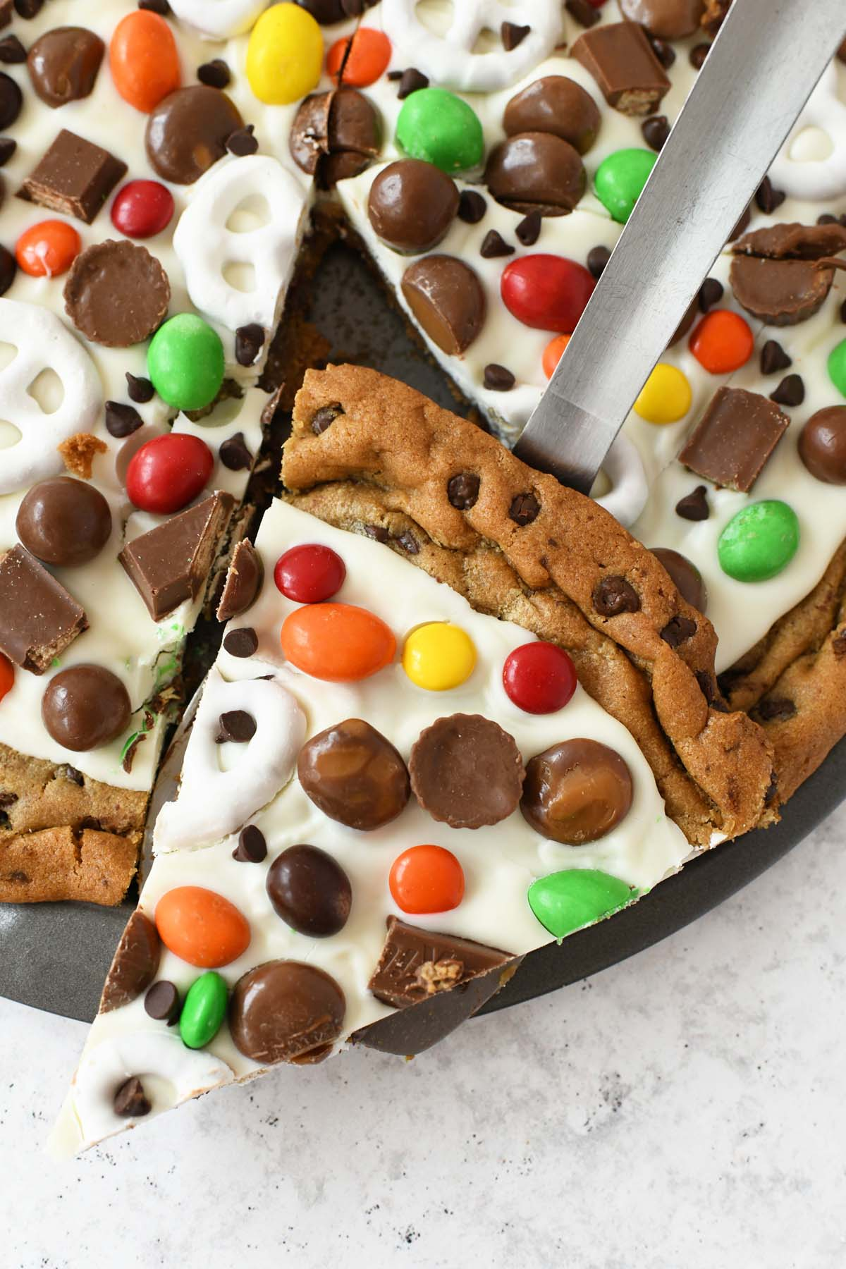 Slice of Candy Chocolate Chip Cookie pizza on a silver spatula.