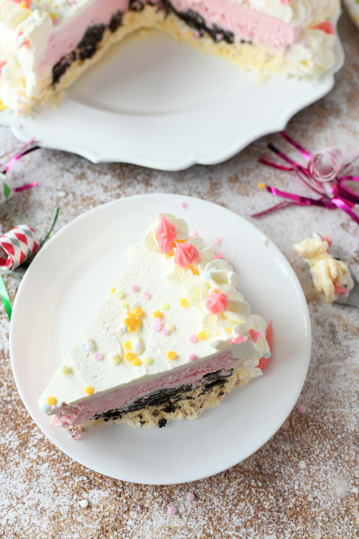 Slice of Homemade Ice Cream Cake on a wooden speckled table with a party streamer.