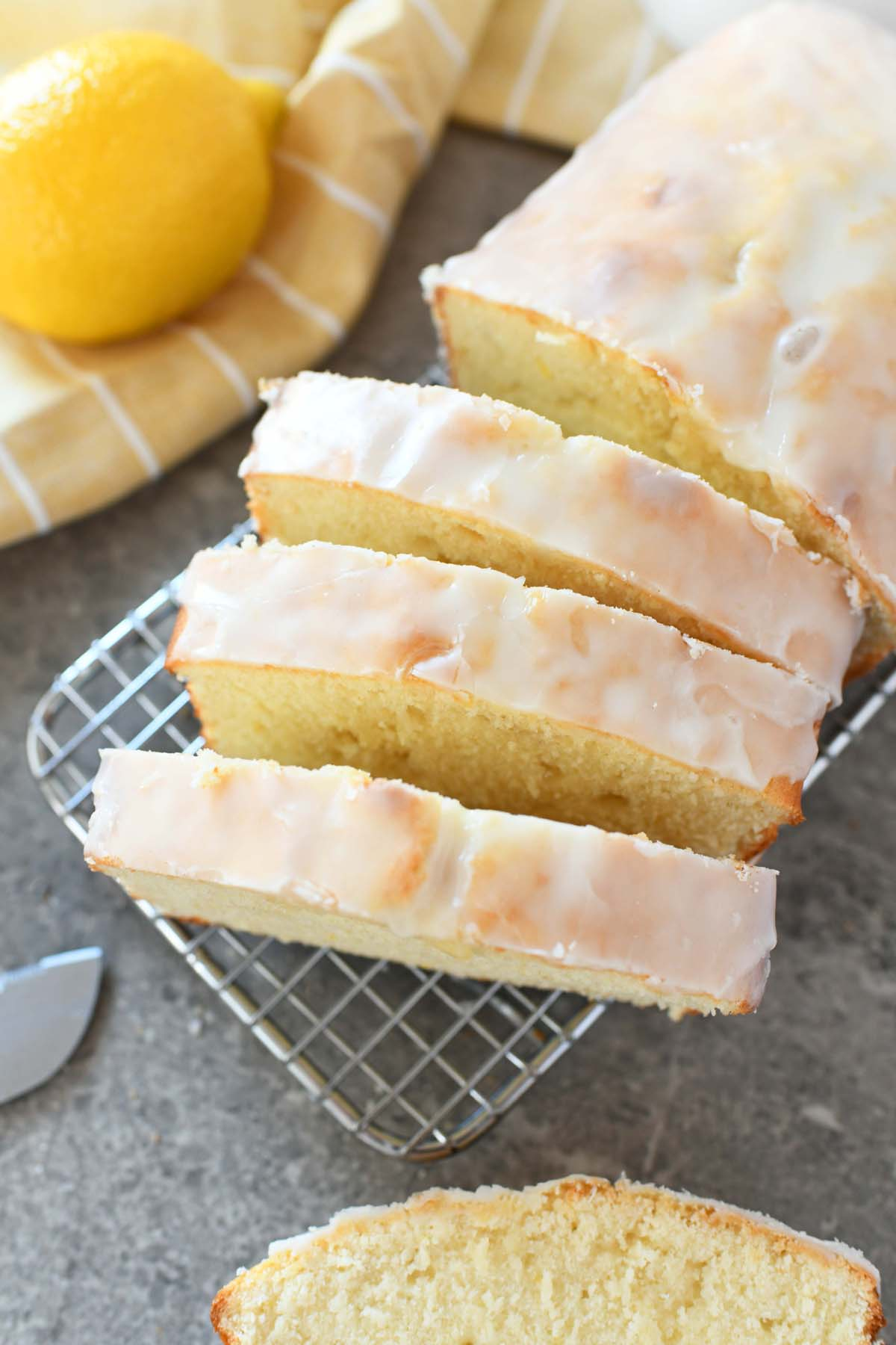 Sliced Lemon pound cake on a cooling rack. There is a yellow lemon, yellow napkin and a knife in this shot.