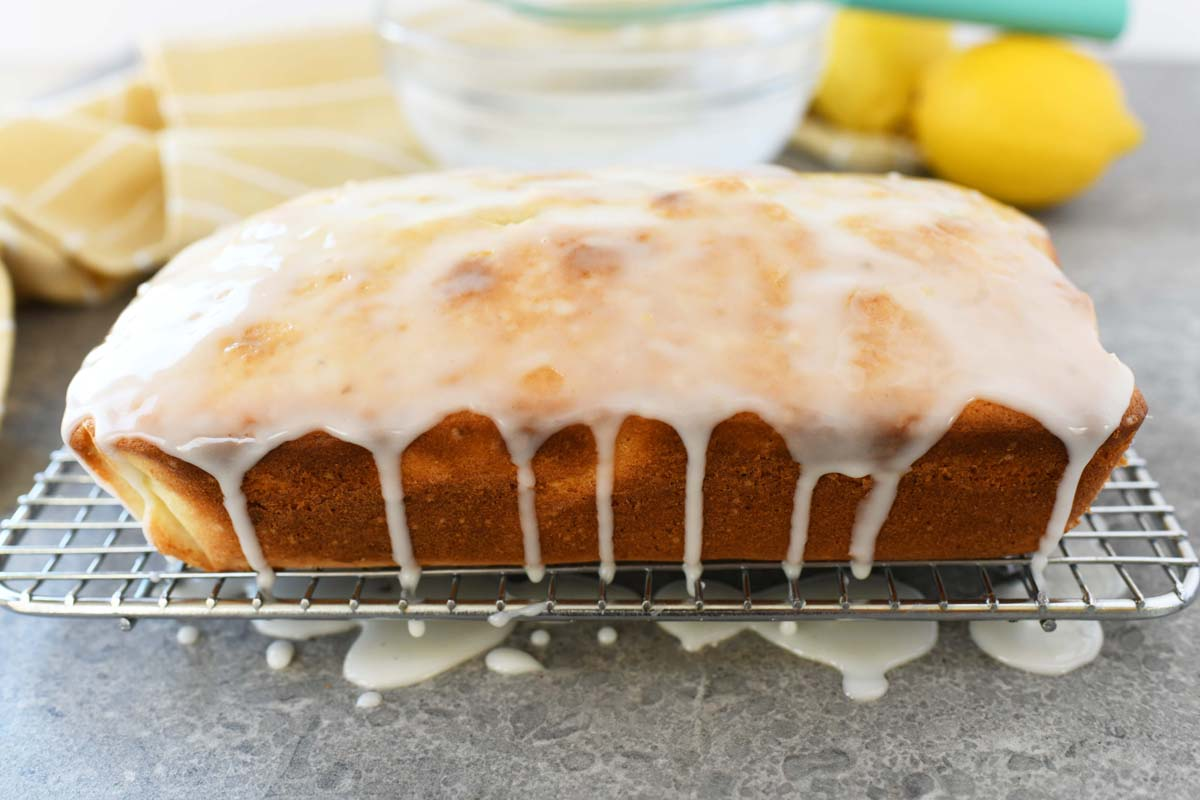 iced lemon loaf cake on a cooling rack with icing drizzling down the sides.