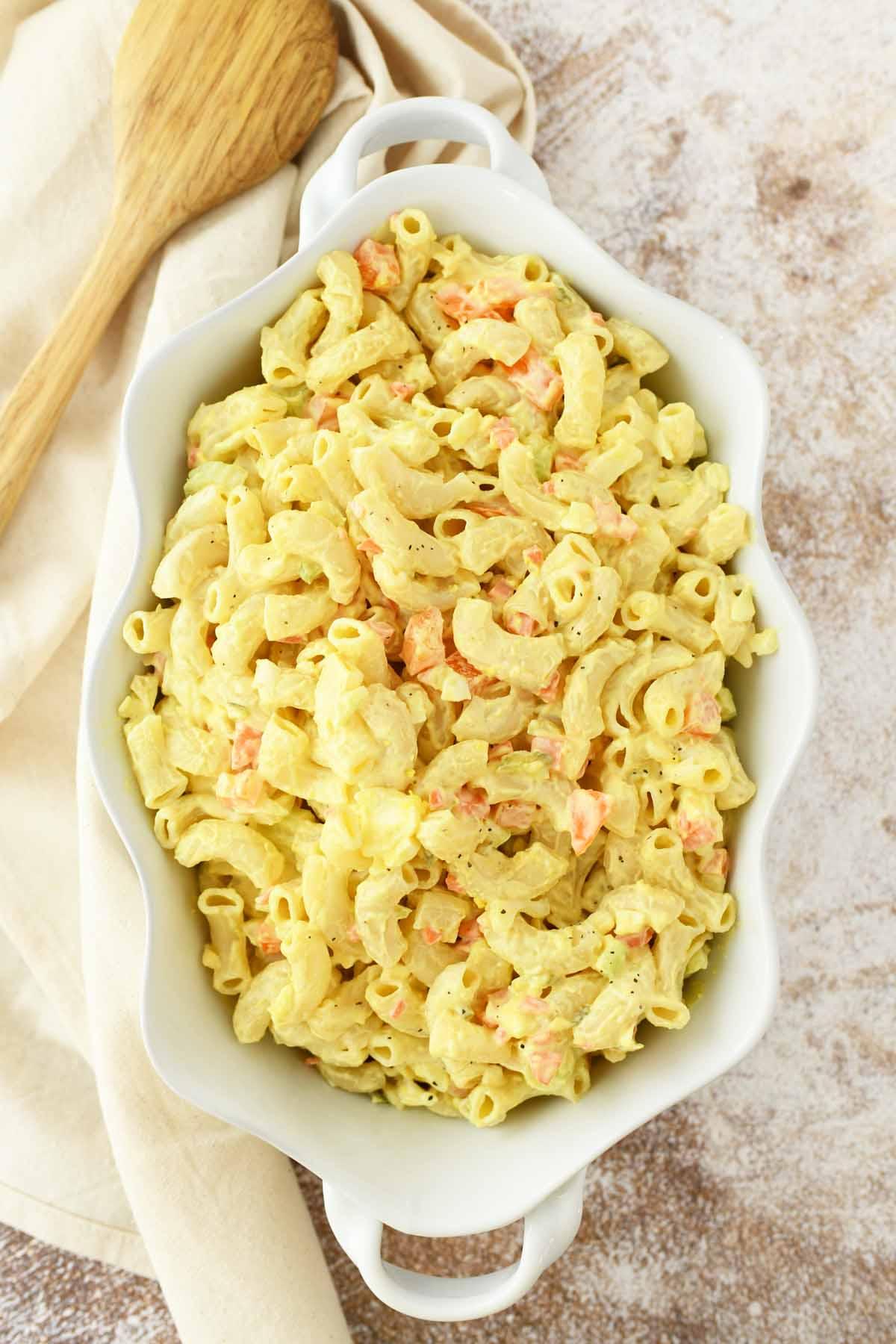 Yellow Macaroni Salad in a white, wavy serving dish.