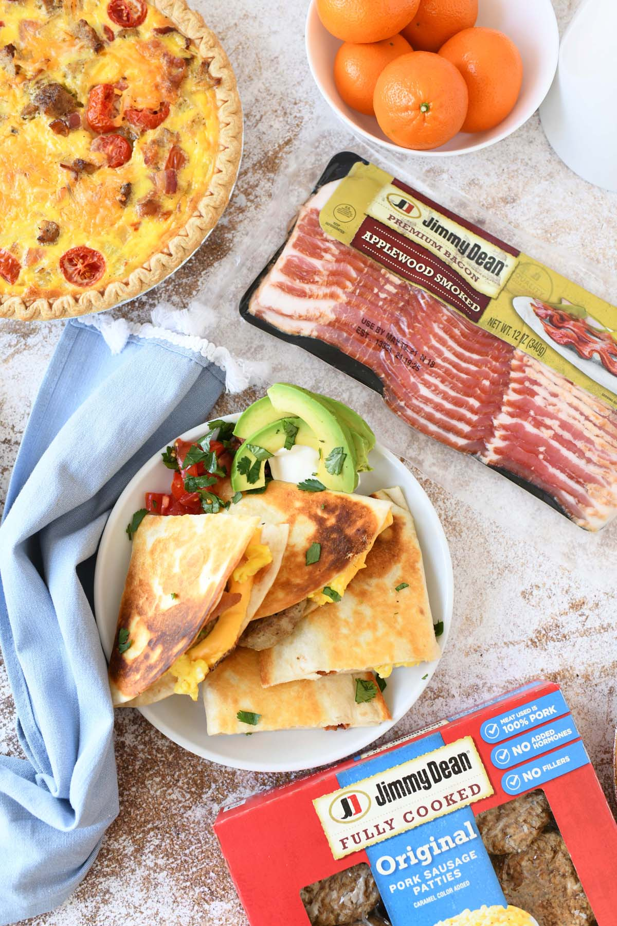 Bacon and Sausage Quesadillas on a white plate with Jimmy Dean Sausage and Bacon nearby.
